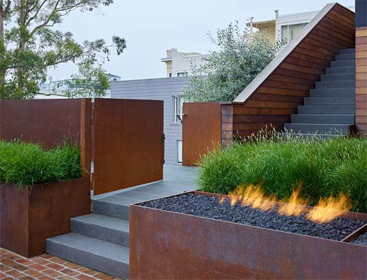 A corten gate, when closed, directs visitors to the front door.