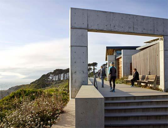The building extends into the landscape, framing dramatic ocean vistas.