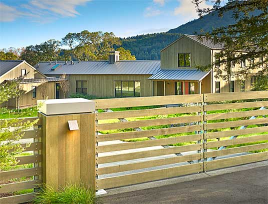The auto gate and columns, clad with resawn, vertical grain Western Red Cedar and powder-coated steel caps, make an understated entry to the property that allows glimpses of the landscape beyond.