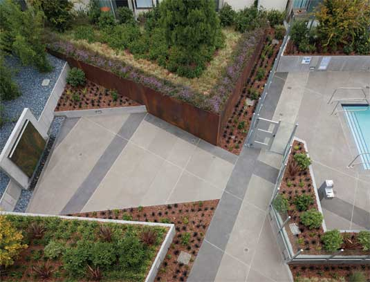 View of courtyard from the roof showing geometric paving pattern in concrete topping slab, corten steel and knife edge concrete planters and pool area.
