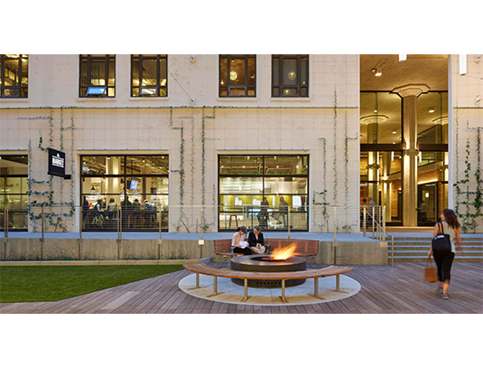 A central fire pit beckons passersby to the refined urban space.