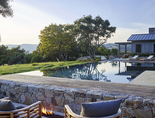 The linear fire pit and stone seat walls at the guest wing terrace with view across the pool to master wing.
