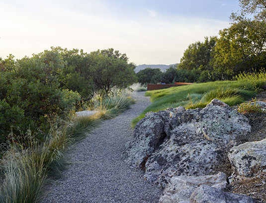 An arcing gravel path leads from both ends of the house past native rock outcroppings to the fire pit.