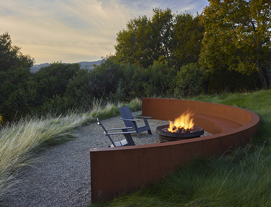 A curved custom steel retaining/seat wall and gas fire pit fashioned from reclaimed quarry equipment set in a native Nassella pulchra meadow.