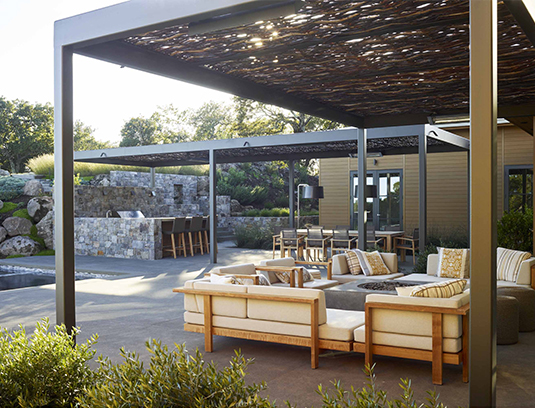 Arbors of woven willow panels set in steel frames provide much needed filtered shade, and help define the outdoor dining room and outdoor living room with custom concrete fire pit.