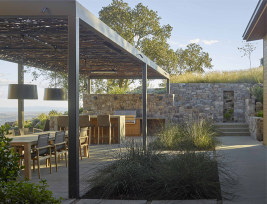 The outdoor dining and outdoor kitchen with shade arbor and heaters.