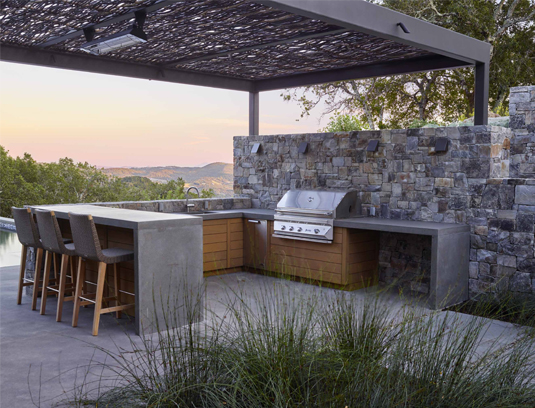 Custom concrete outdoor kitchen counters echo the stone waterfall kitchen island, accented with the same horizontal cedar as the buildings.