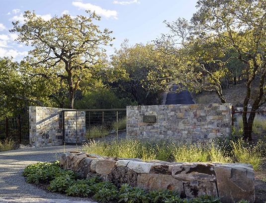 Low gently curving walls utilize on-site boulders fit together in the Incan style. Taller entry walls and an automatic steel gate provide security and announce the entry into the property.