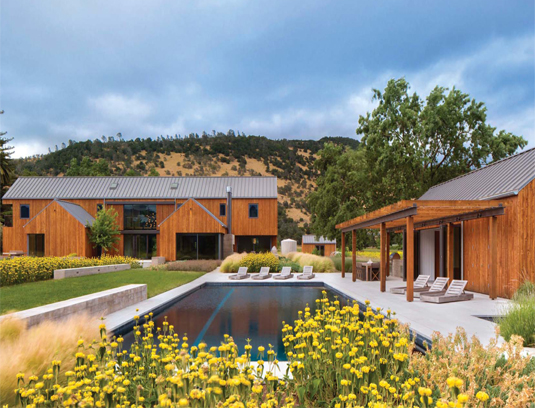 The modern farmhouse inspired buildings frame the pool and garden spaces. Concrete seat walls create informal seating areas.