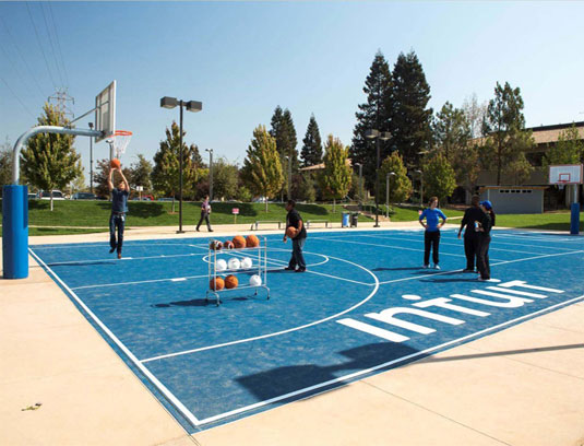 One football field worth of parking lots were converted to employee amenity space, including this basketball court and yoga loan. Achieved through coordination with the city and client to increase electric vehicle stations, transit options and existing stall restriping.