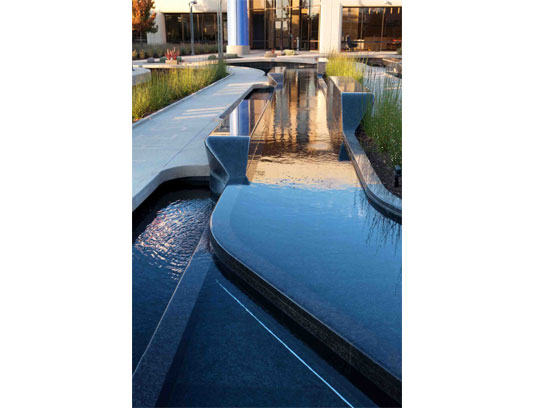 The entry rain garden creates an elegant and sustainable arrival statement for the campus. This includes ribbon-like granite wiers with integral seating of solid stone.