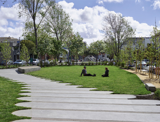 The walkway cuts diagonally through the meadow, which is carefully graded to achieve the feeling of one big space. Granite blocks, unearthed during construction, are integrated into the paving to signal material transitions, protect planting, and to offer low seating.